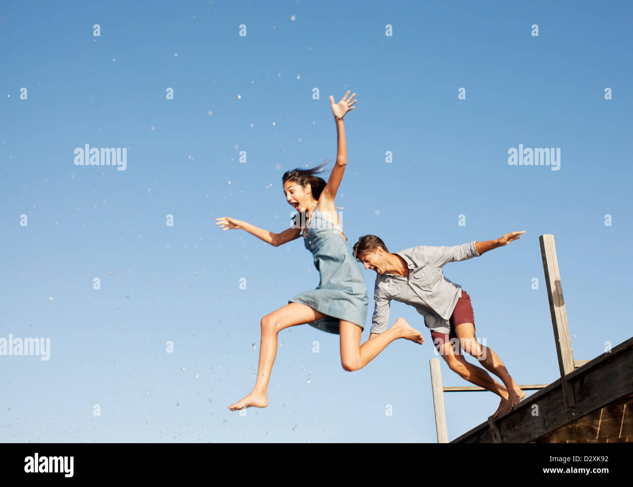 Exuberant couple jumping off dock - Stock Image