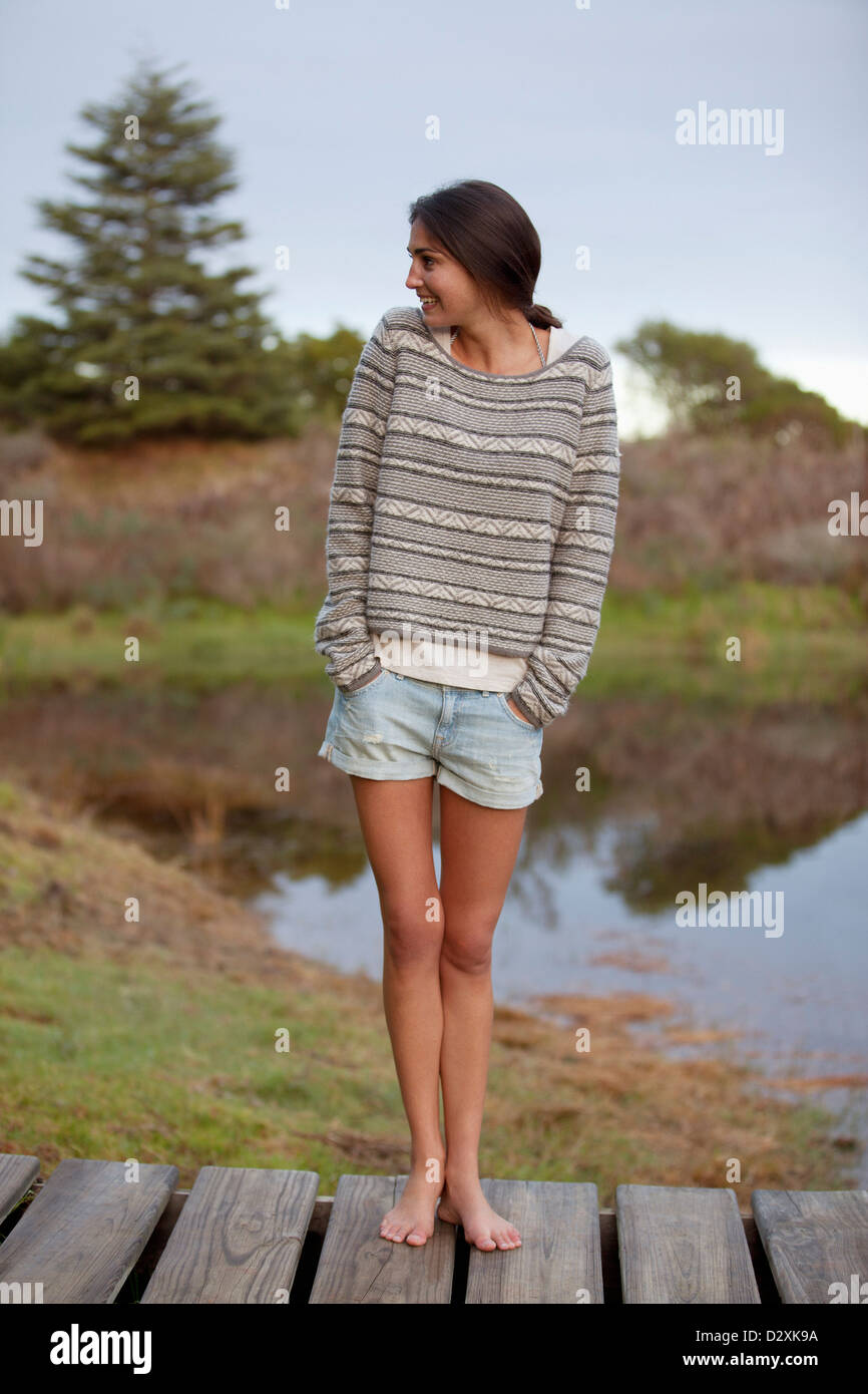 Smiling woman standing on dock with hands in short pockets Stock Photo