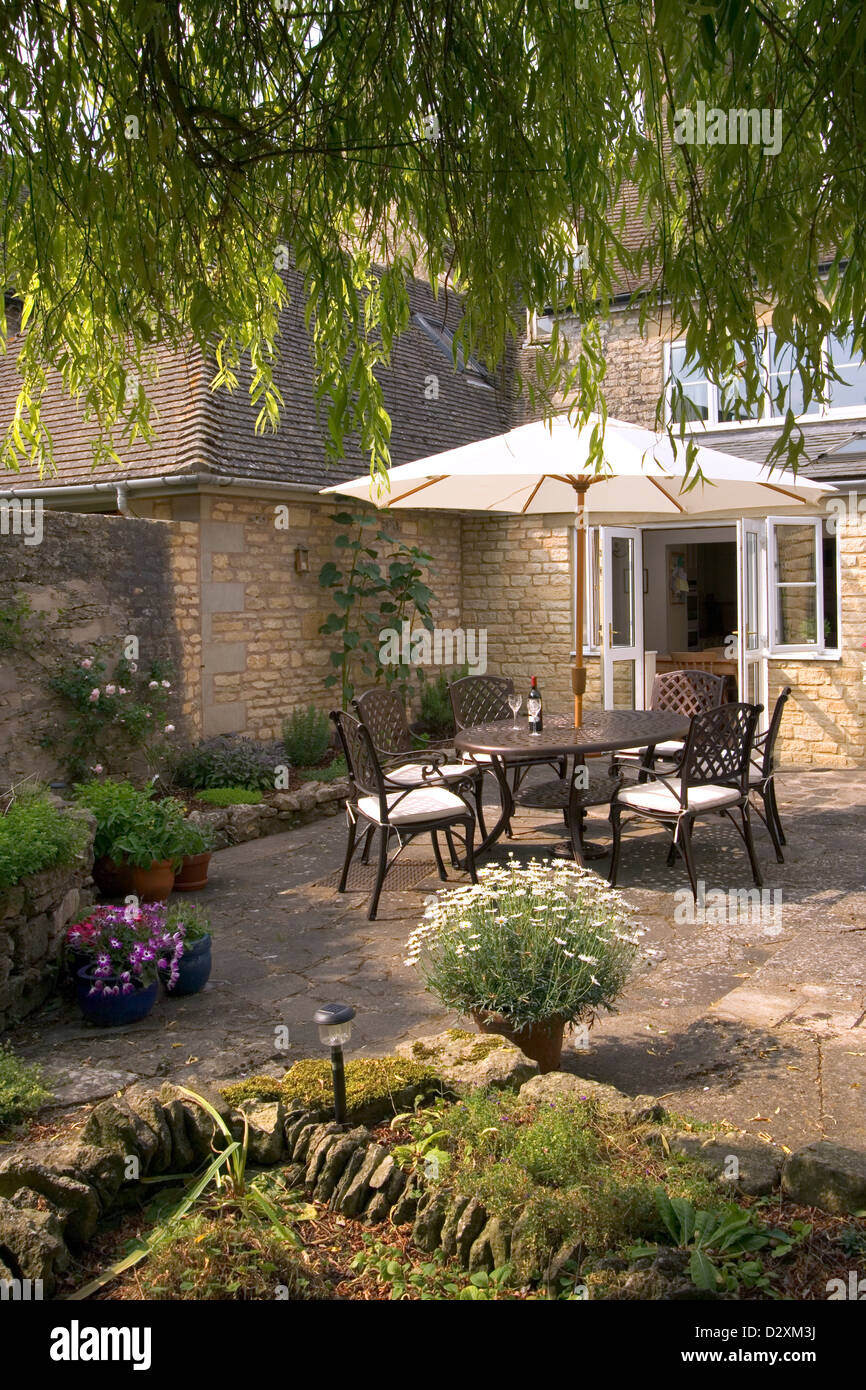 A Secluded Garden Patio With Garden Table And Chairs And Sunshade Umbrella.