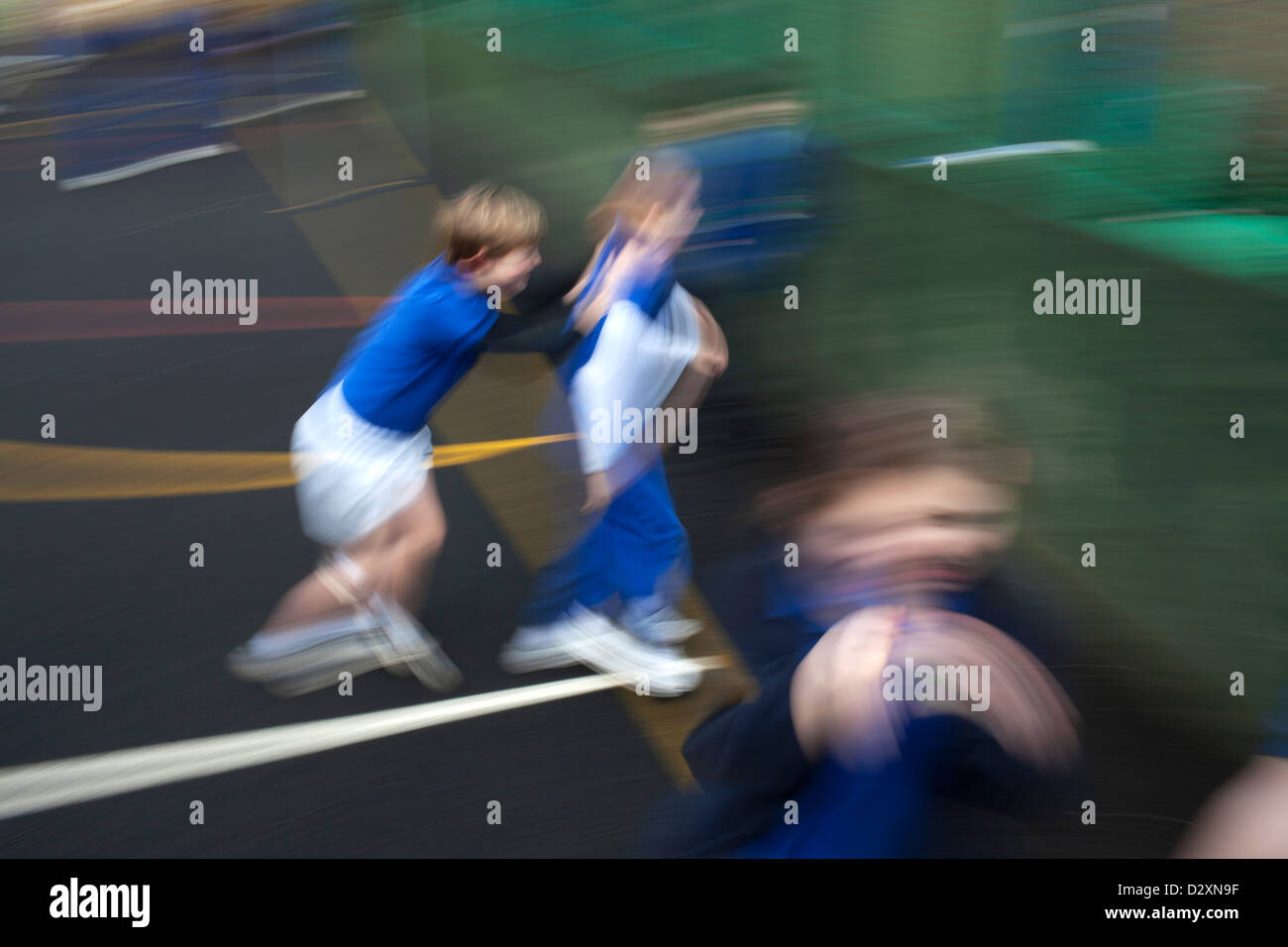 primary school children playing in palyground - Stock Image
