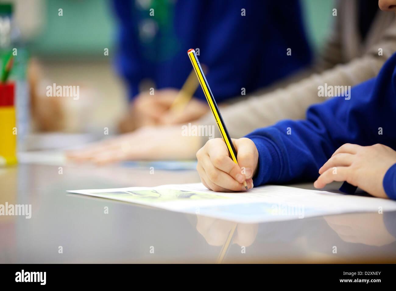 primary school boy writing on work sheet in classroom Stock Photo