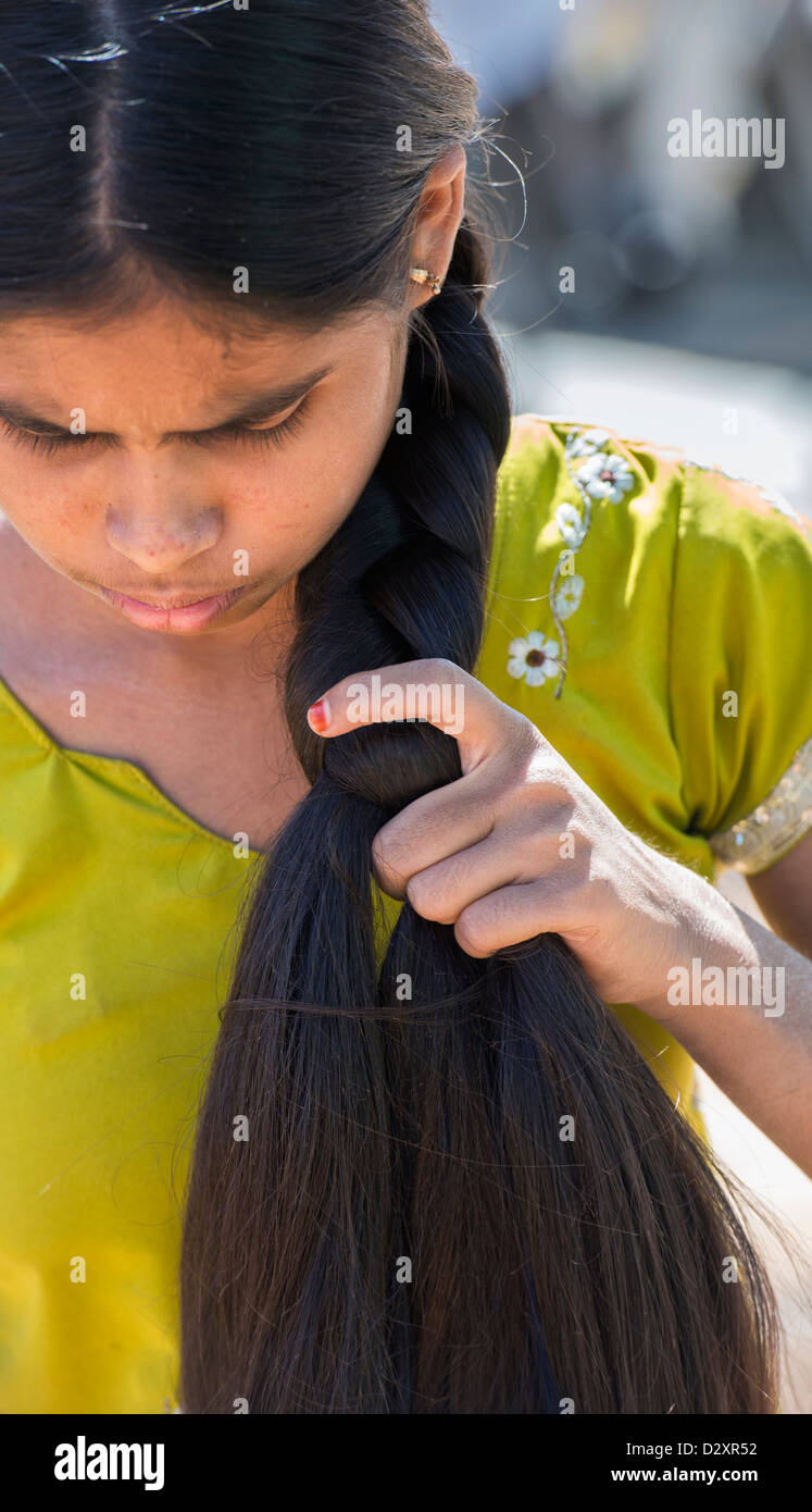 rural indian village girl plaiting her long hair. andhra pradesh