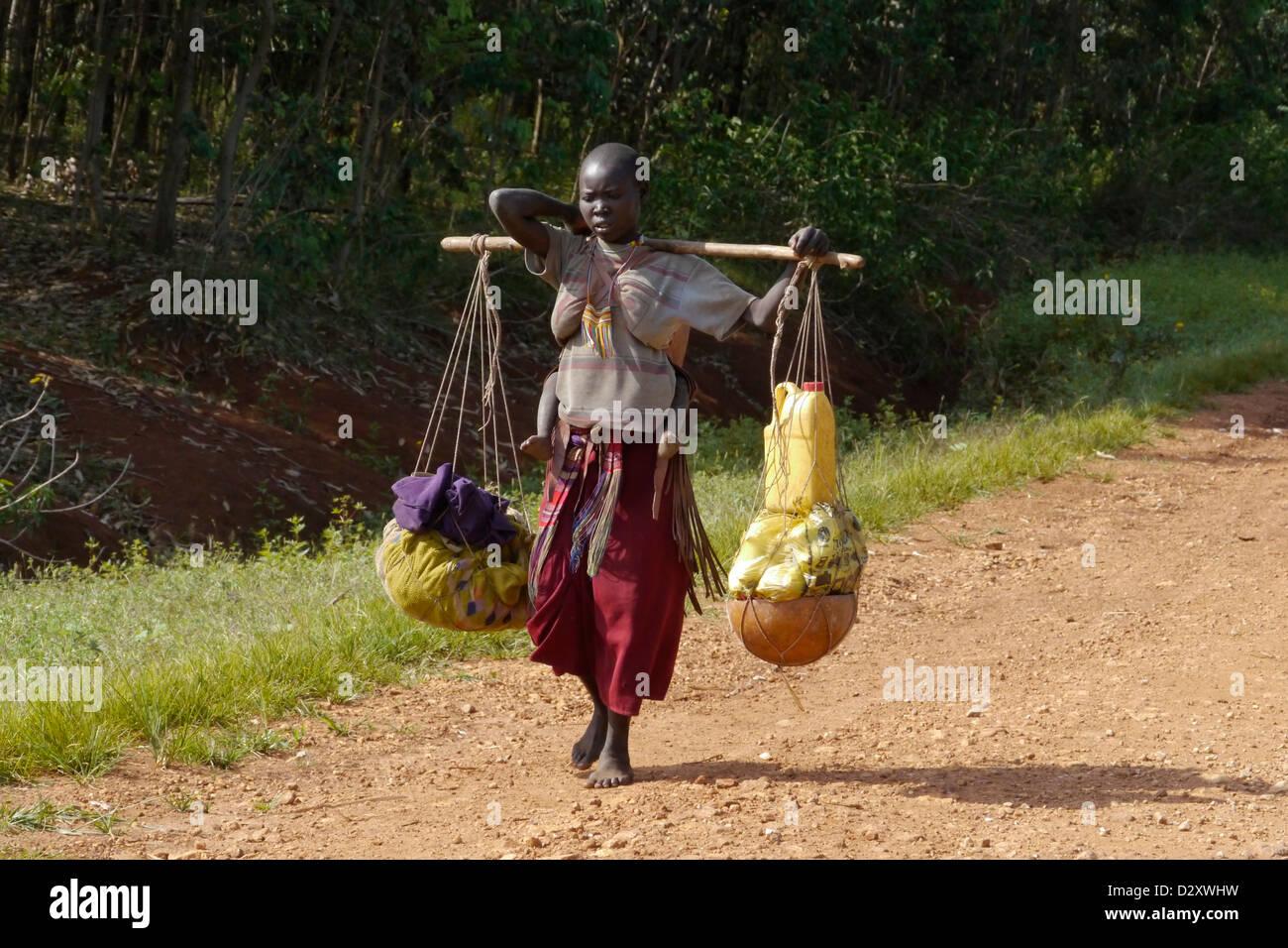 ethiopia road between chagni debate beni shangul gumuz region woman female carrying good or market transport Stock Photo