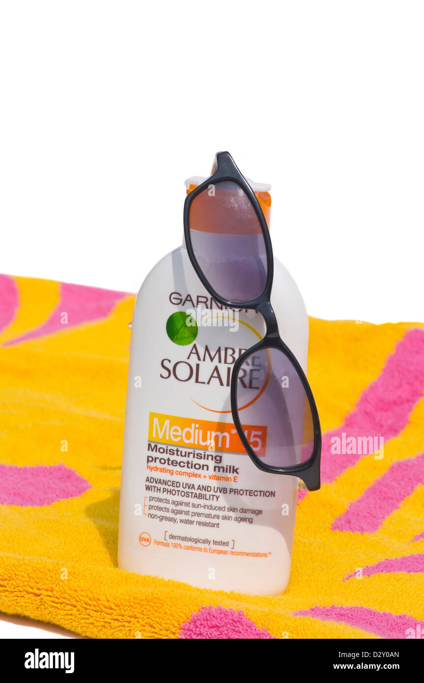 Beach Towel A Bottle Of Suncream and A Pair Of Sunglasses - Stock Image