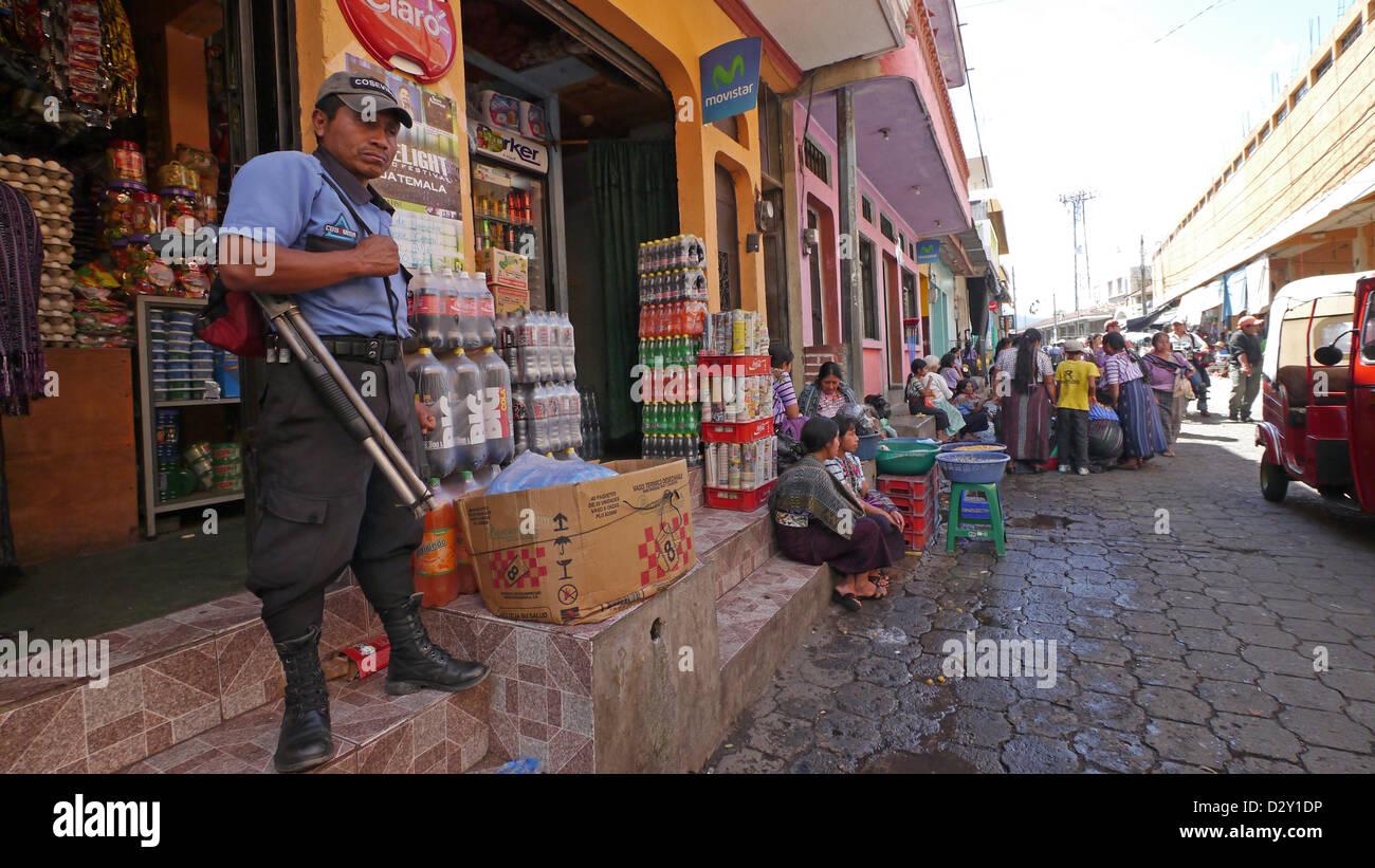 mayan market scenes santiago atitlan shop guarded by armed man male latin america central economy trade gun - Stock Image