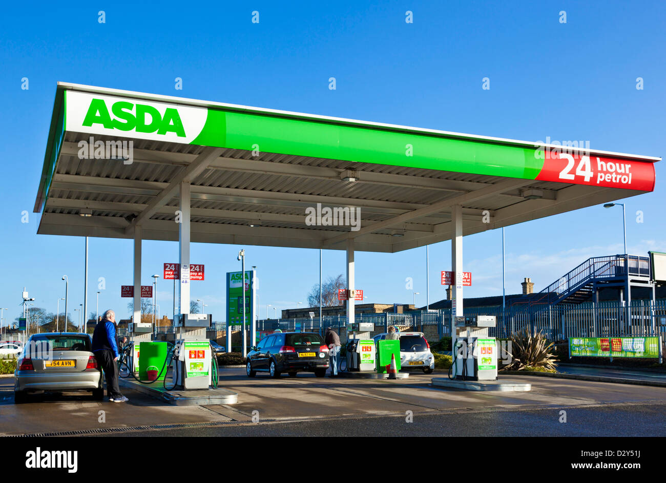 asda petrol station forecourt with man putting petrol in his car uk - Stock Image