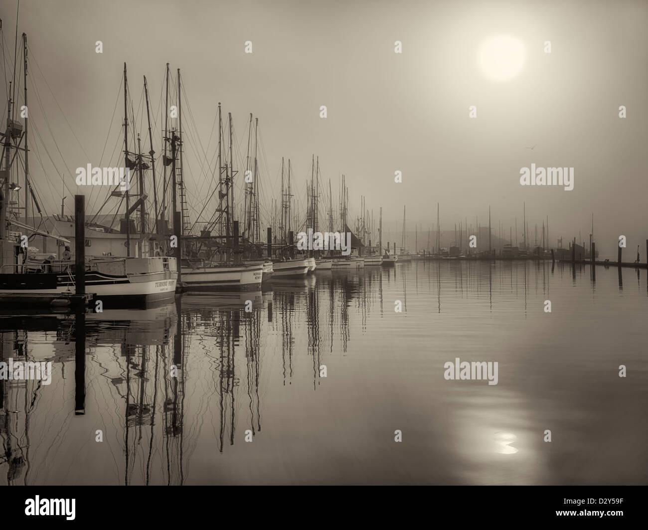 Sunrise through fog with boats at Newport Harbor. Oregon - Stock Image