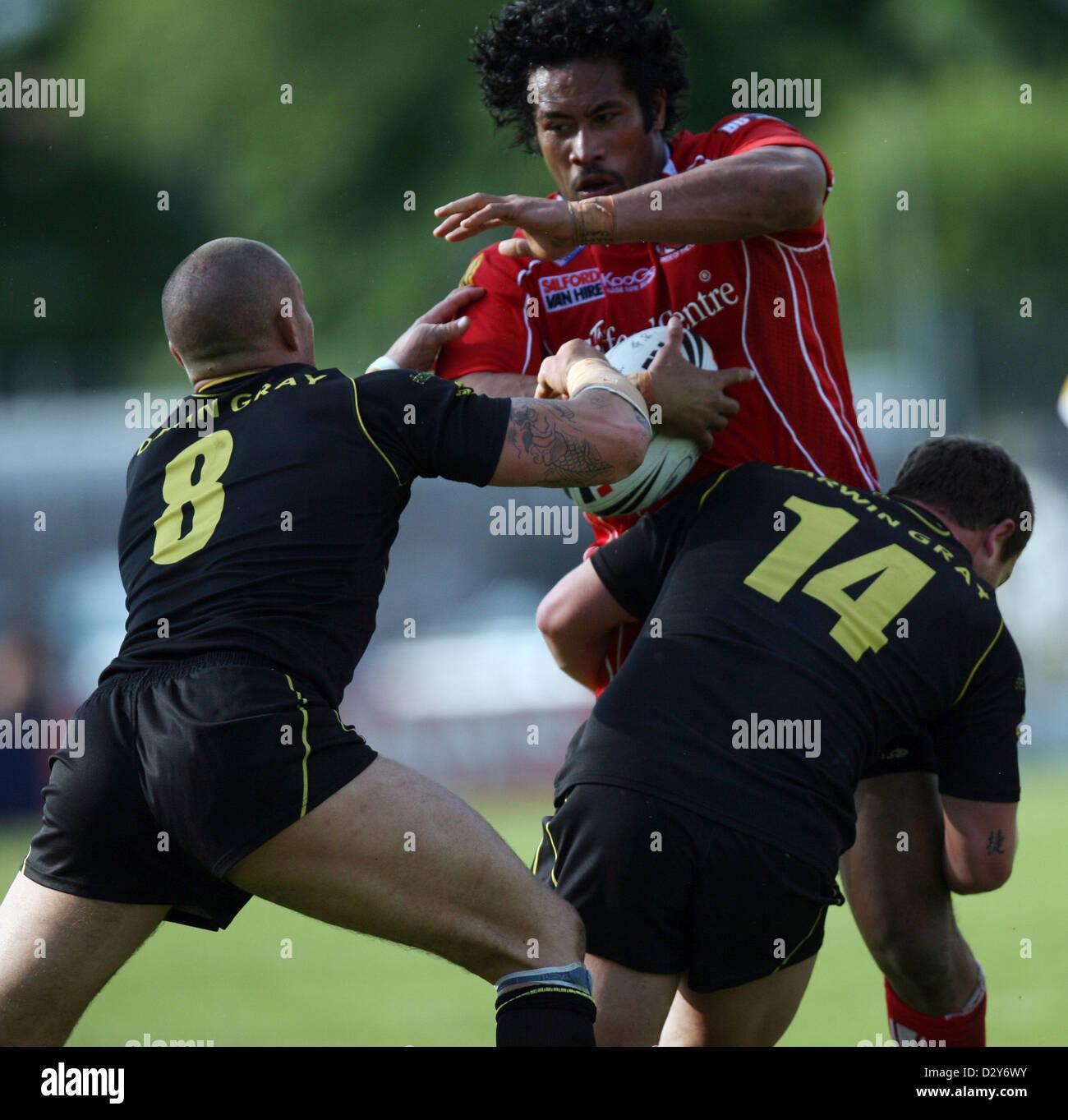 Celtic Crusaders v Salford City Reds. Reds' Phil Leuluai tries to get past tacklers Crusaders' Jordan James - Stock Image