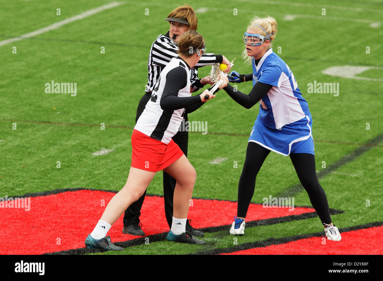 A Catholic University player (L) and Marymount University player (R) get set for a faceoff during a college lacrosse - Stock Image
