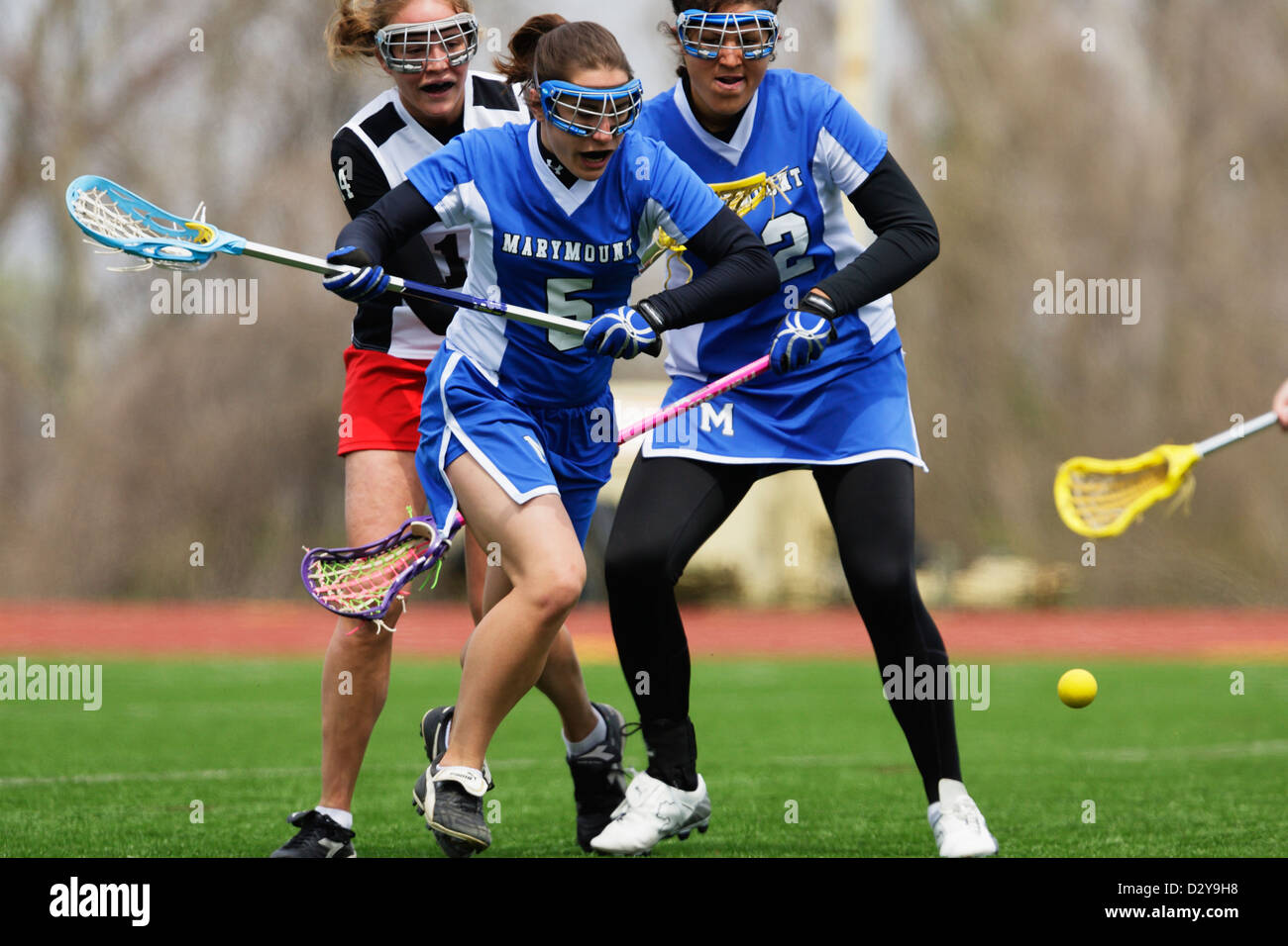 Catholic University and Marymount University players chase the ball during a lacrosse game at at Catholic University. - Stock Image