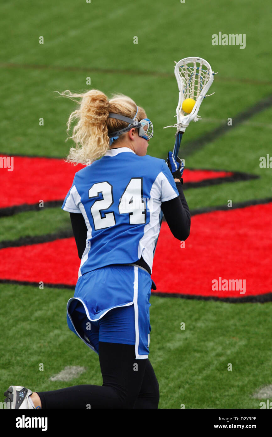 A Marymount University lacrosse player in action against Catholic University. - Stock Image