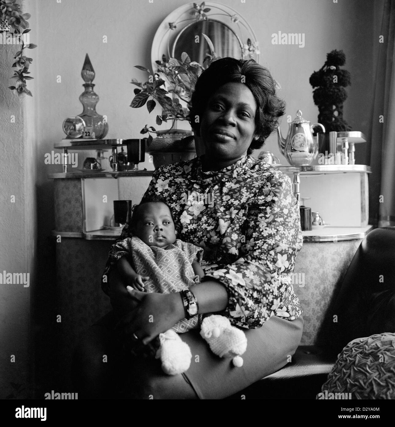 Portrait of a proud Afro-Caribbean British mother with her baby in her living room in Leeds West Yorkshire England - Stock Image