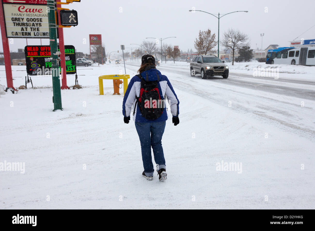 woman wearing backpack walking along 8th street in snowstorm Saskatoon Saskatchewan Canada - Stock Image
