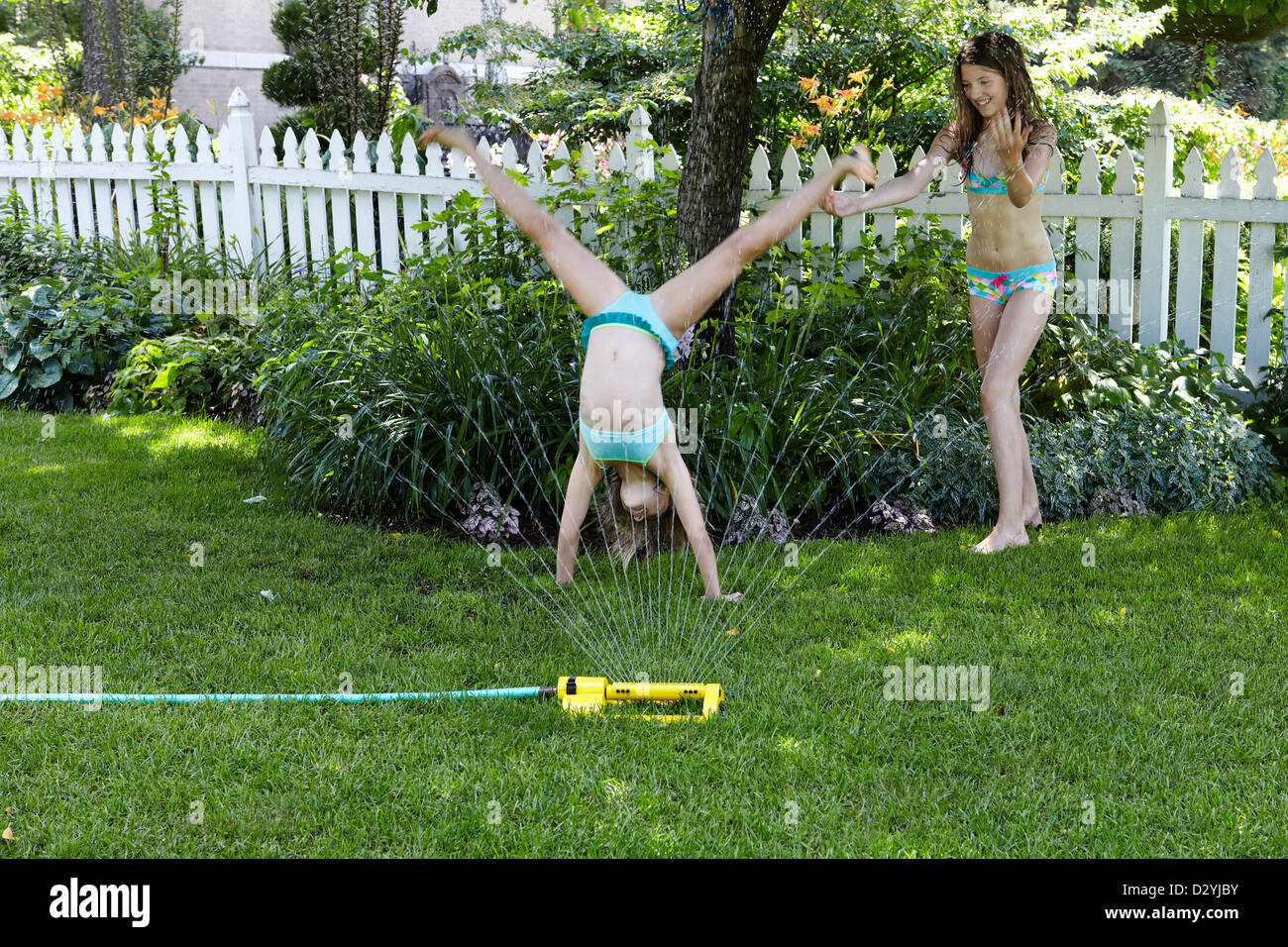 Sisters playing in water from sprinkler - Stock Image