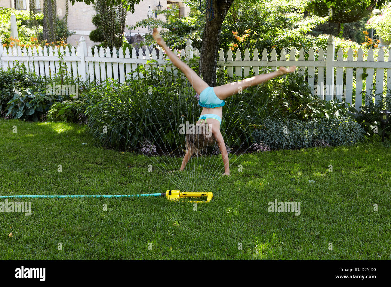 9 year old girl doing cartwheel on lawn - Stock Image