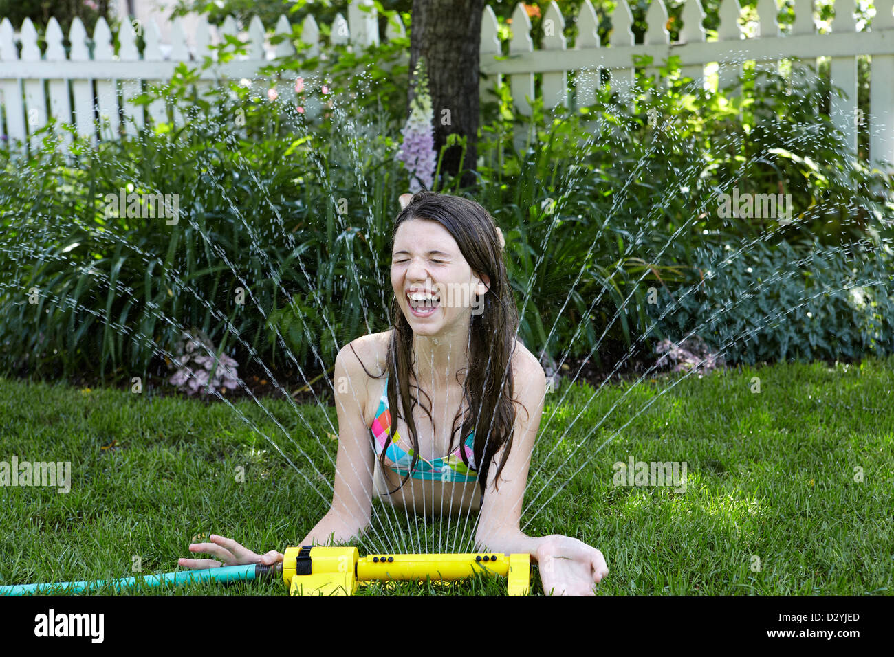 12 year old girl playing with water sprinkler. - Stock Image