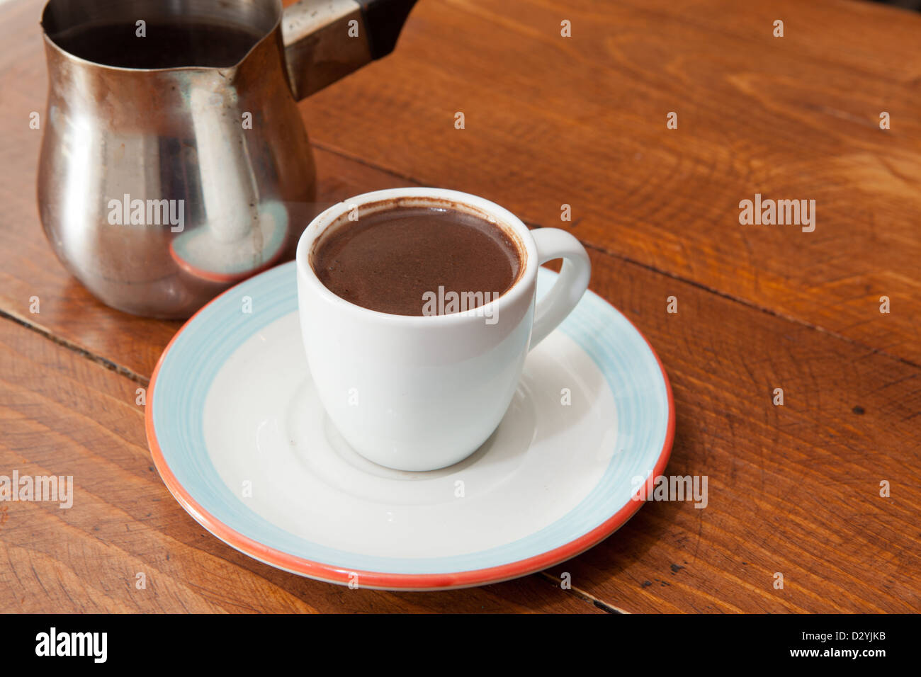 Demitasse cup of rich and robust Turkish or Arabic coffee served with metal carafe. - Stock Image