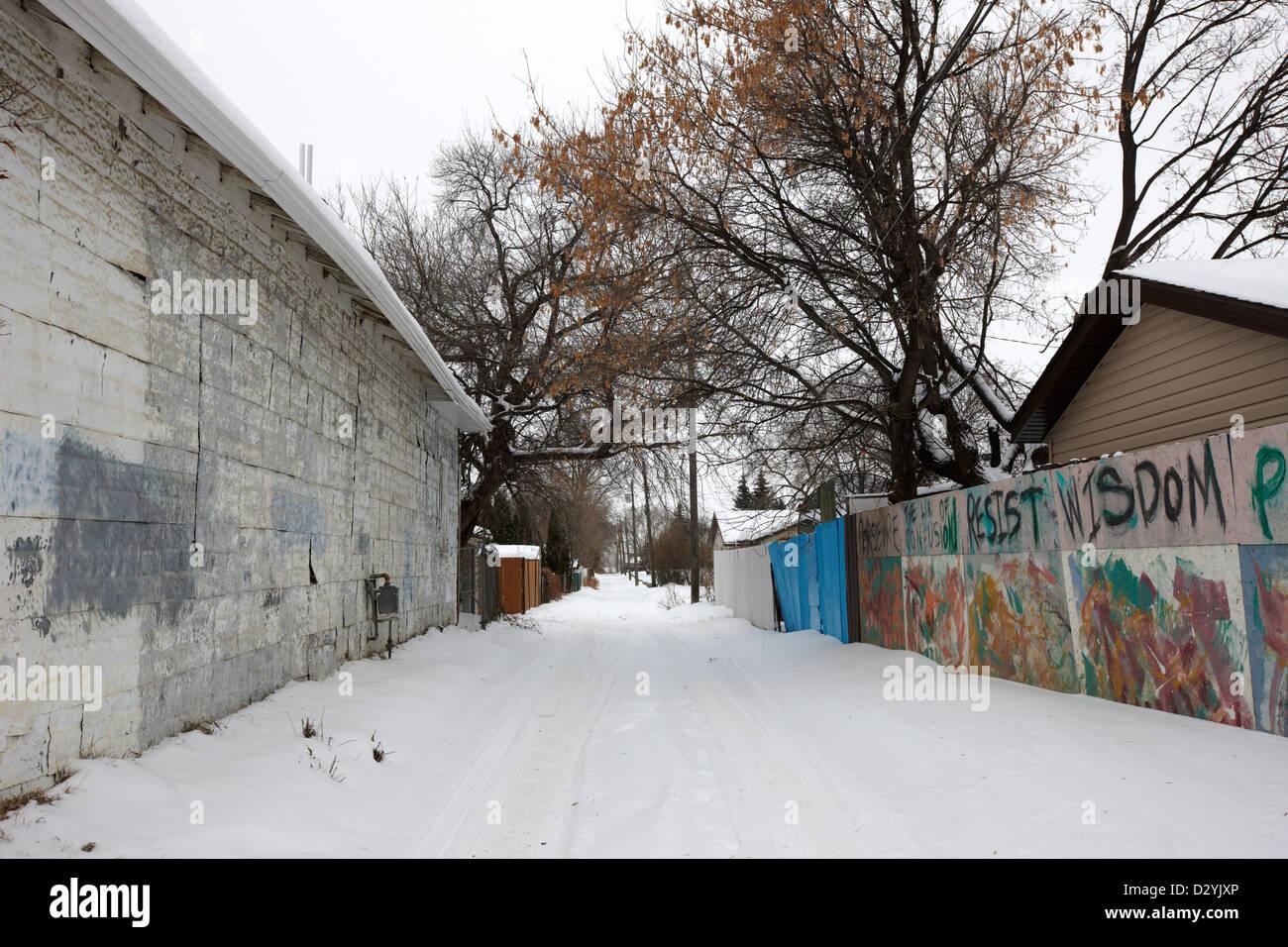 snow covered rear alleyway between houses in Saskatoon Saskatchewan Canada - Stock Image
