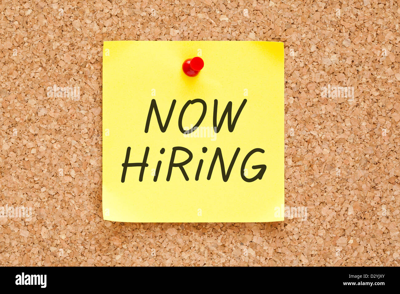 Now Hiring written on an yellow sticky note pinned with red push pin on cork bulletin board. - Stock Image