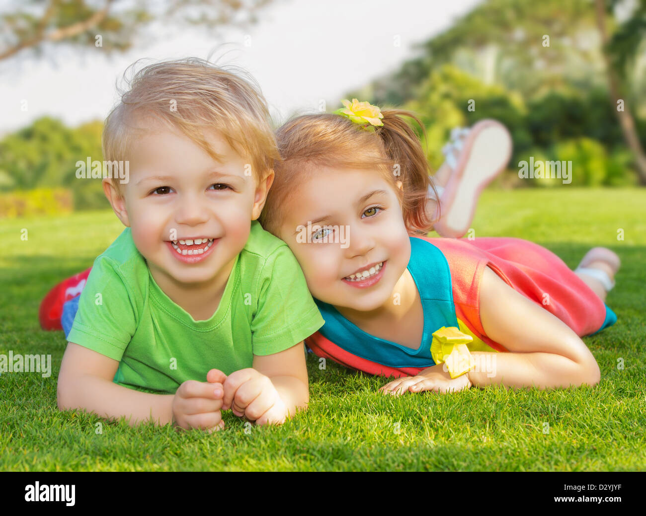 Picture of brother and sister having fun in the park, two cheerful child laying down on green grass, little girl - Stock Image