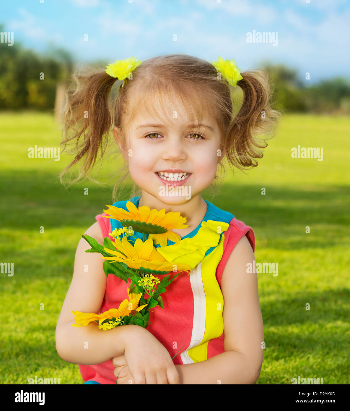 picture of cute happy little girl wearing colorful dress and holding