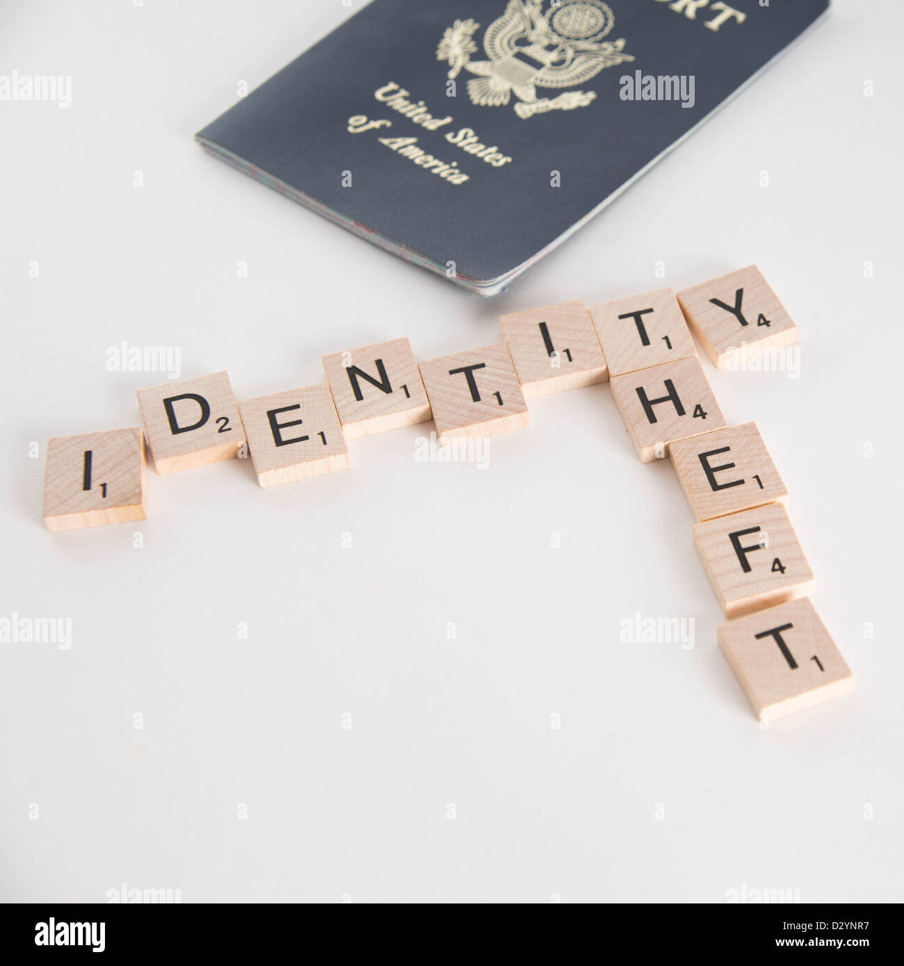 Identity theft spelled in Scrabble letters with US passport out of focus in the background. Isolated on white background. - Stock Image