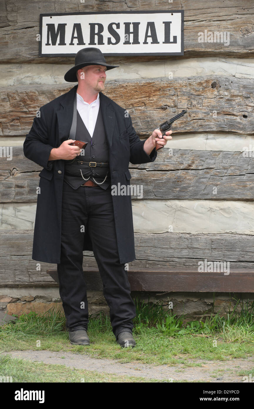 Marshal in the old American west standing watch with pistols drawn, authentic reenactor portrayal of sheriff Wyatt - Stock Image
