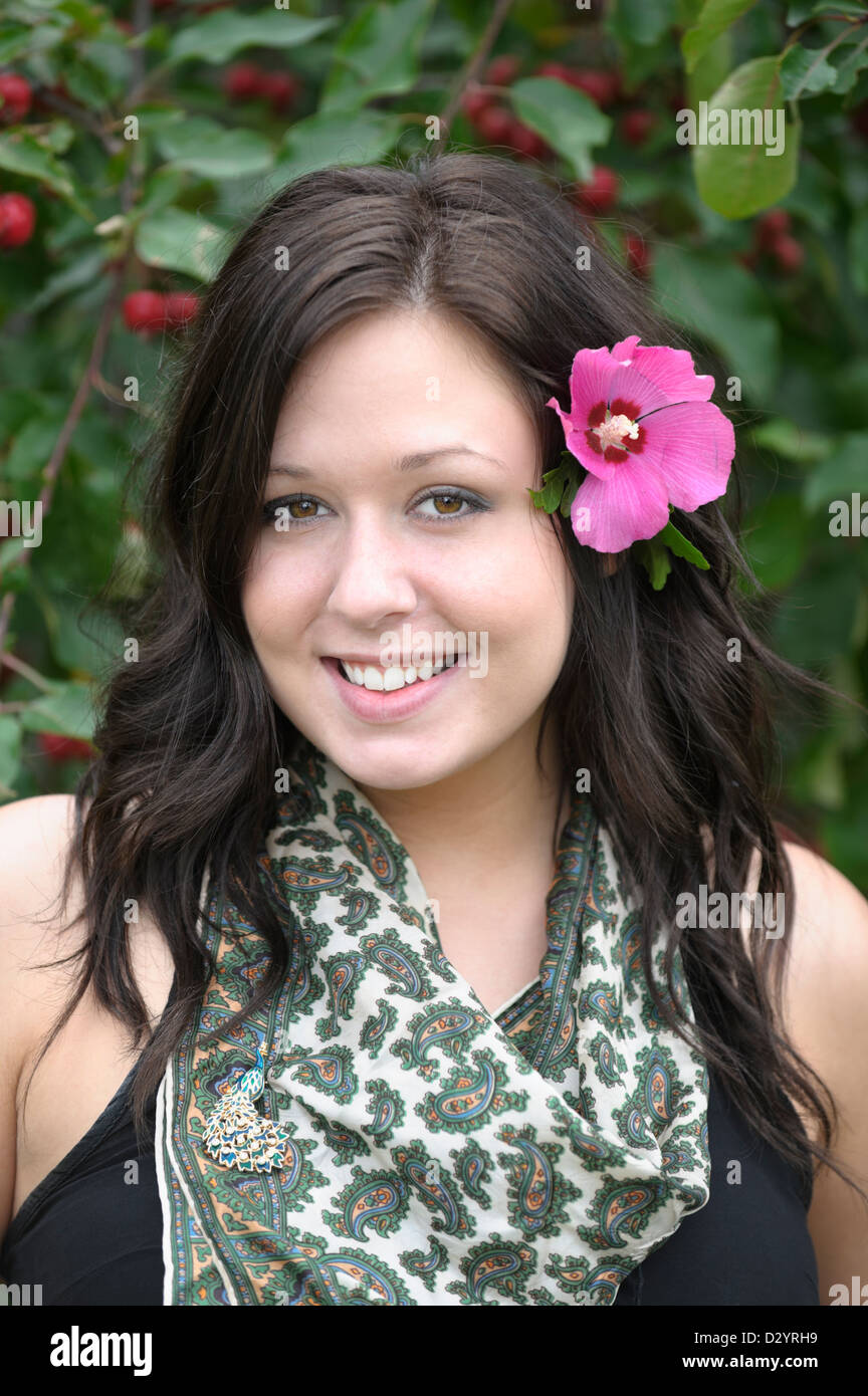 Girl with flower in her hair, portrait head and shoulders shot of pretty brunette in her early twenties. - Stock Image