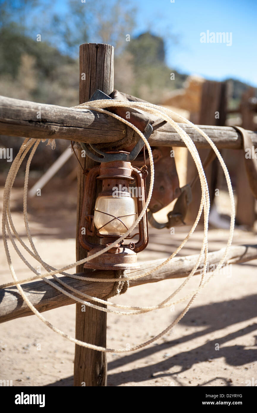A lasso and an old gas lantern on a wood fence at an old west dude ranch - Stock Image