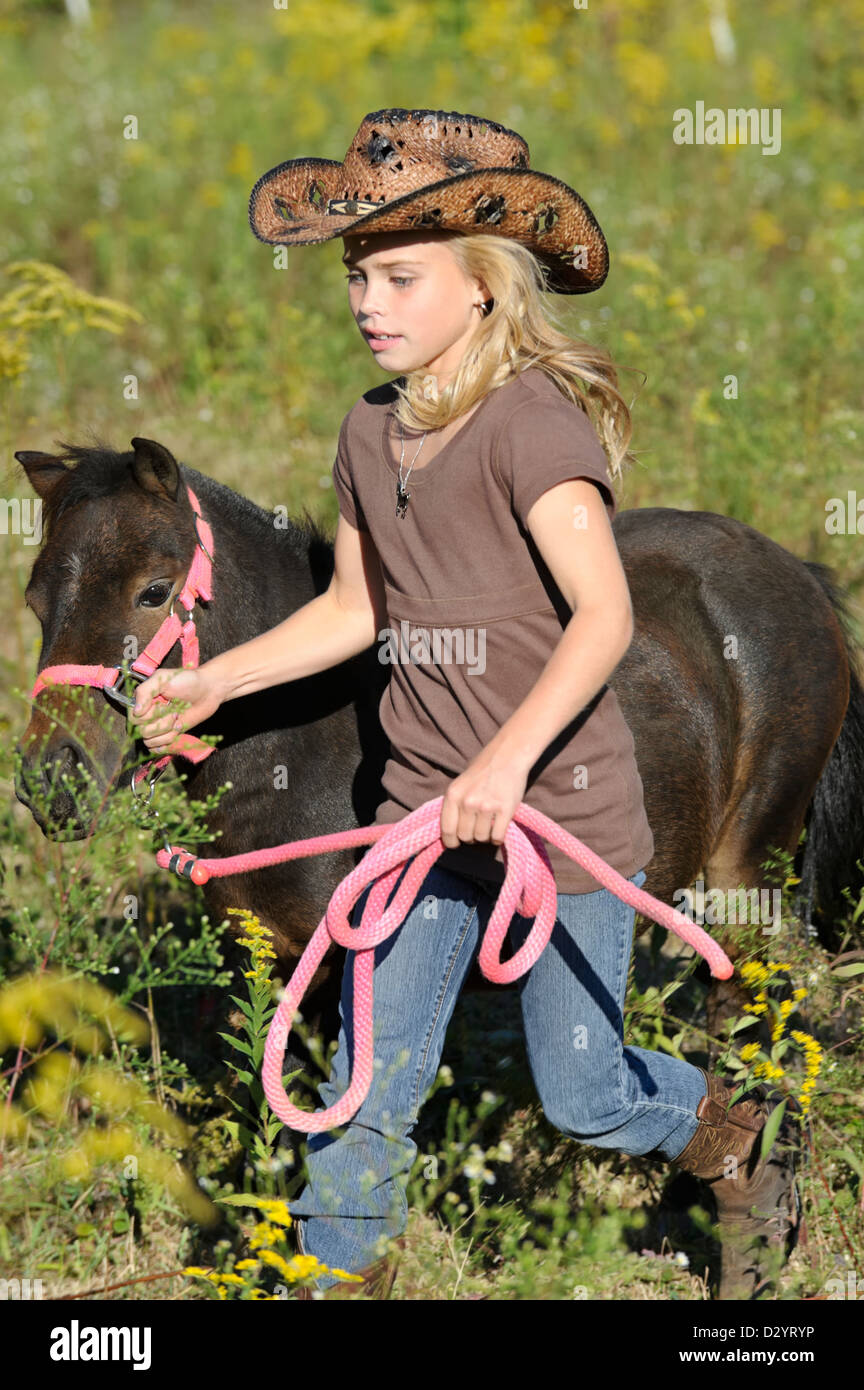Girl running miniature horse through summer goldenrod field in late  afternoon 07fba5b68163