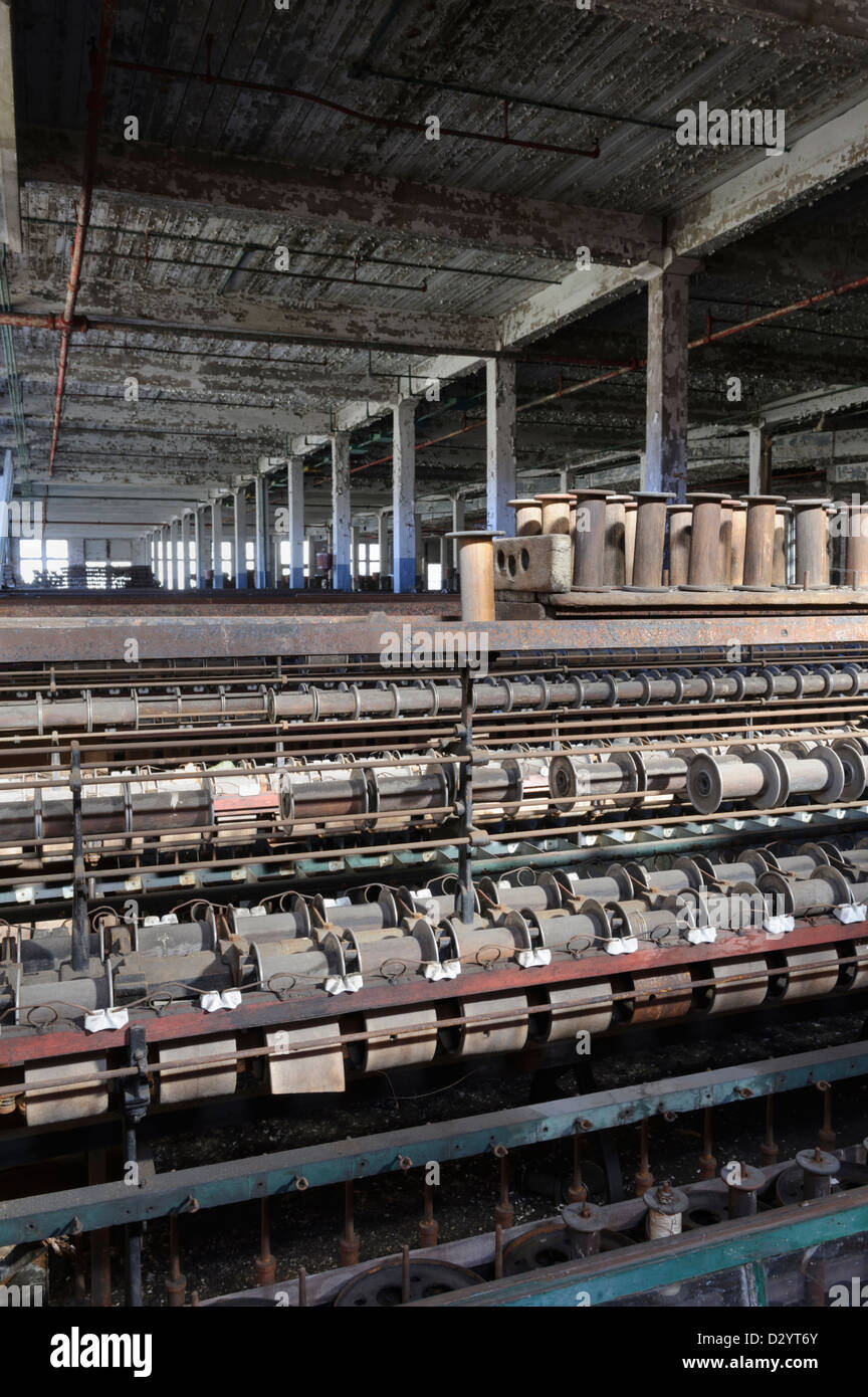 Textile mill machinery sits stopped in an empty closed and abandoned American factory. - Stock Image