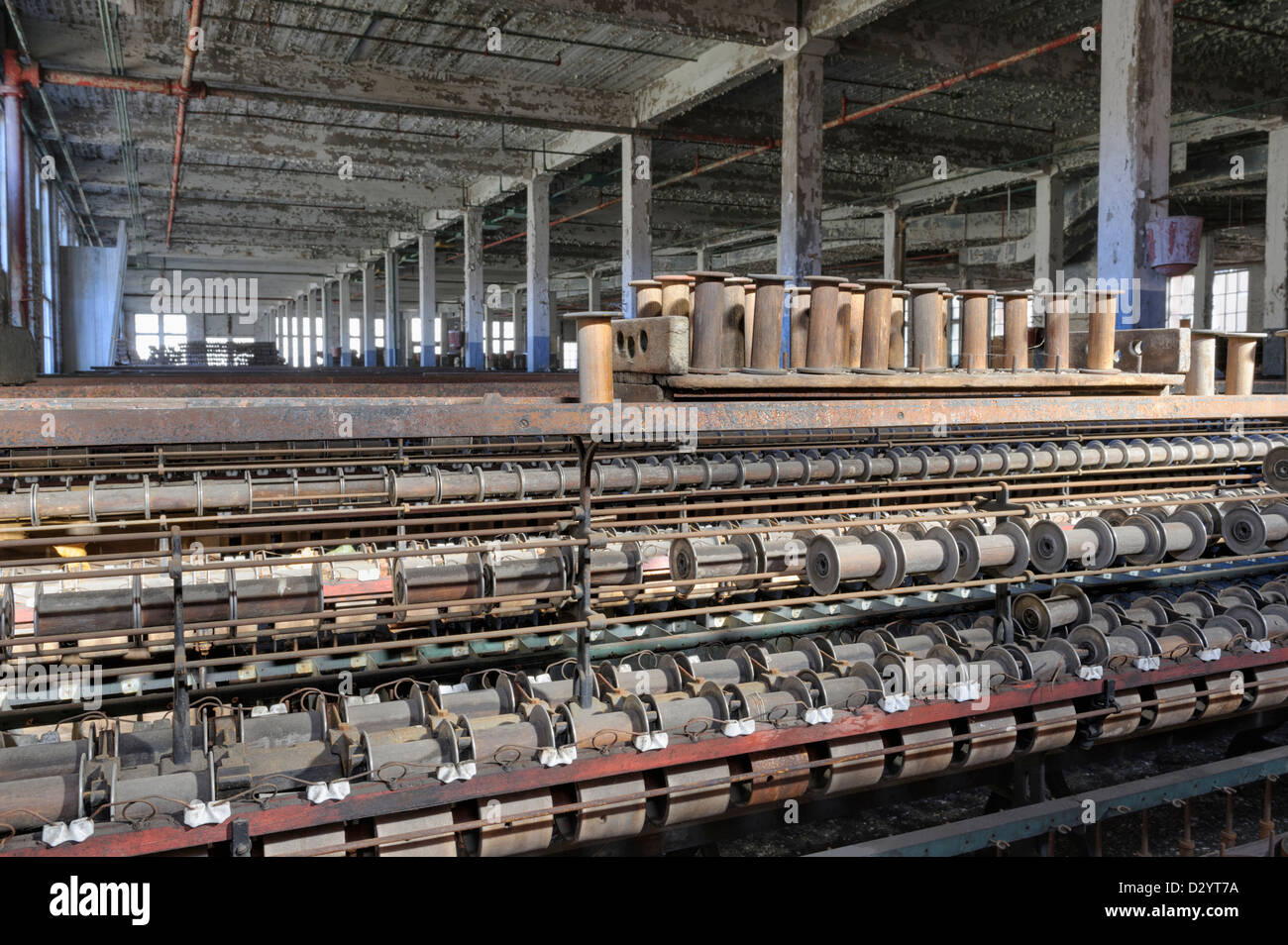 Textile mill cloth weaving machinery sits stopped in an empty closed and abandoned American factory. - Stock Image