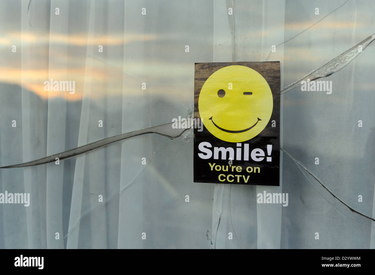 A 'Smile! You're on CCTV' sticker on a broken window - Stock Image