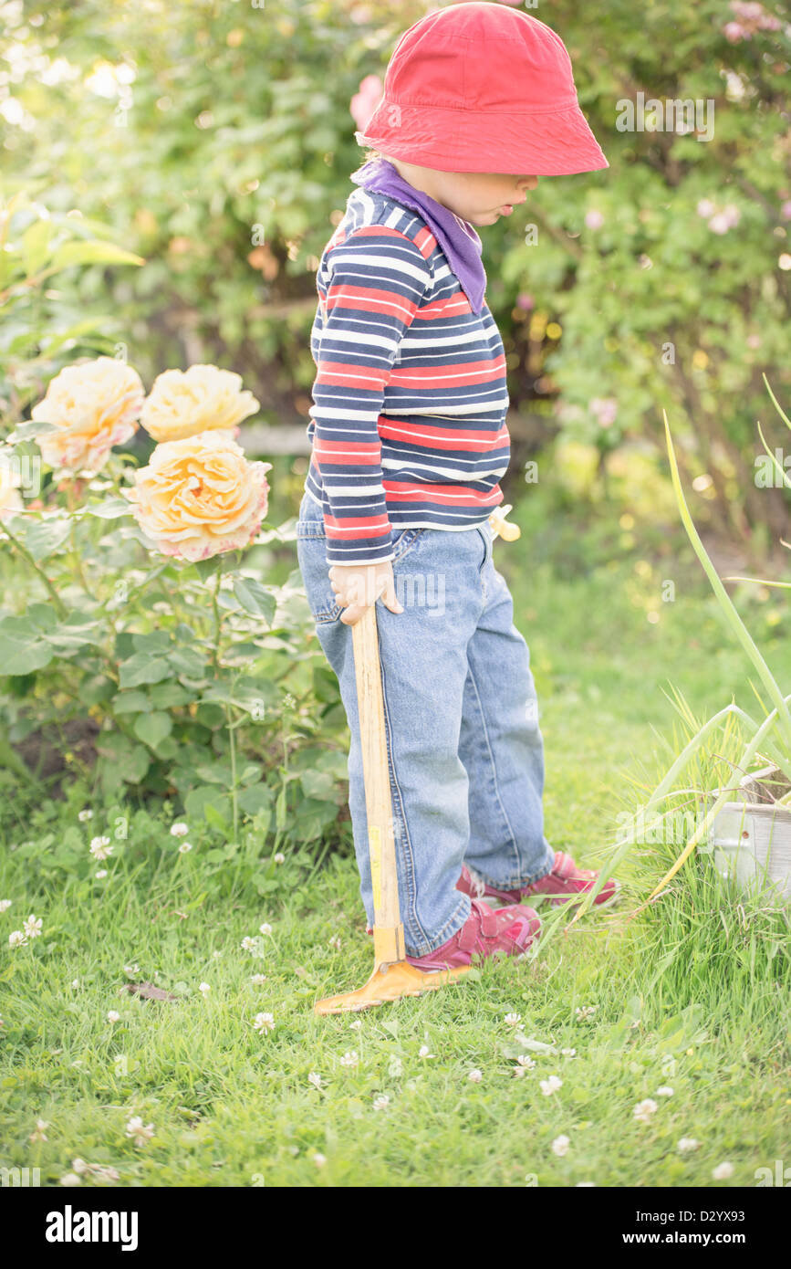 Small child 3 years old playing in a garden and exploring the plants, Sweden. - Stock Image