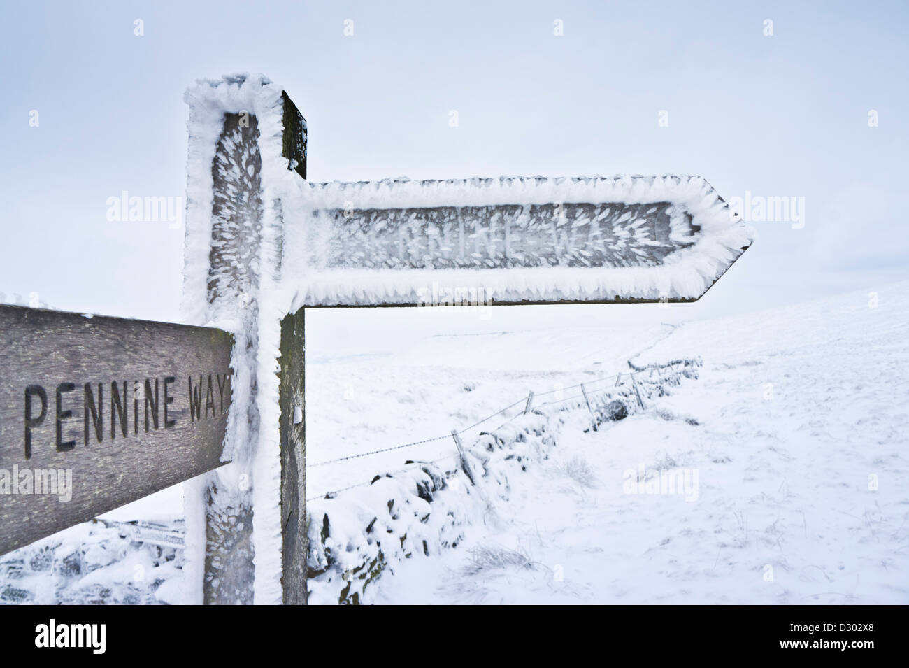 snow and ice covered signpost giving directions to the pennine way Edale cross Kinder scout Derbyshire peak district - Stock Image