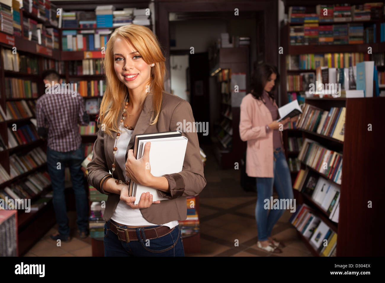 close-up of young attractive caucasian girl in bookshop holding two different colored books in her hands with other - Stock Image