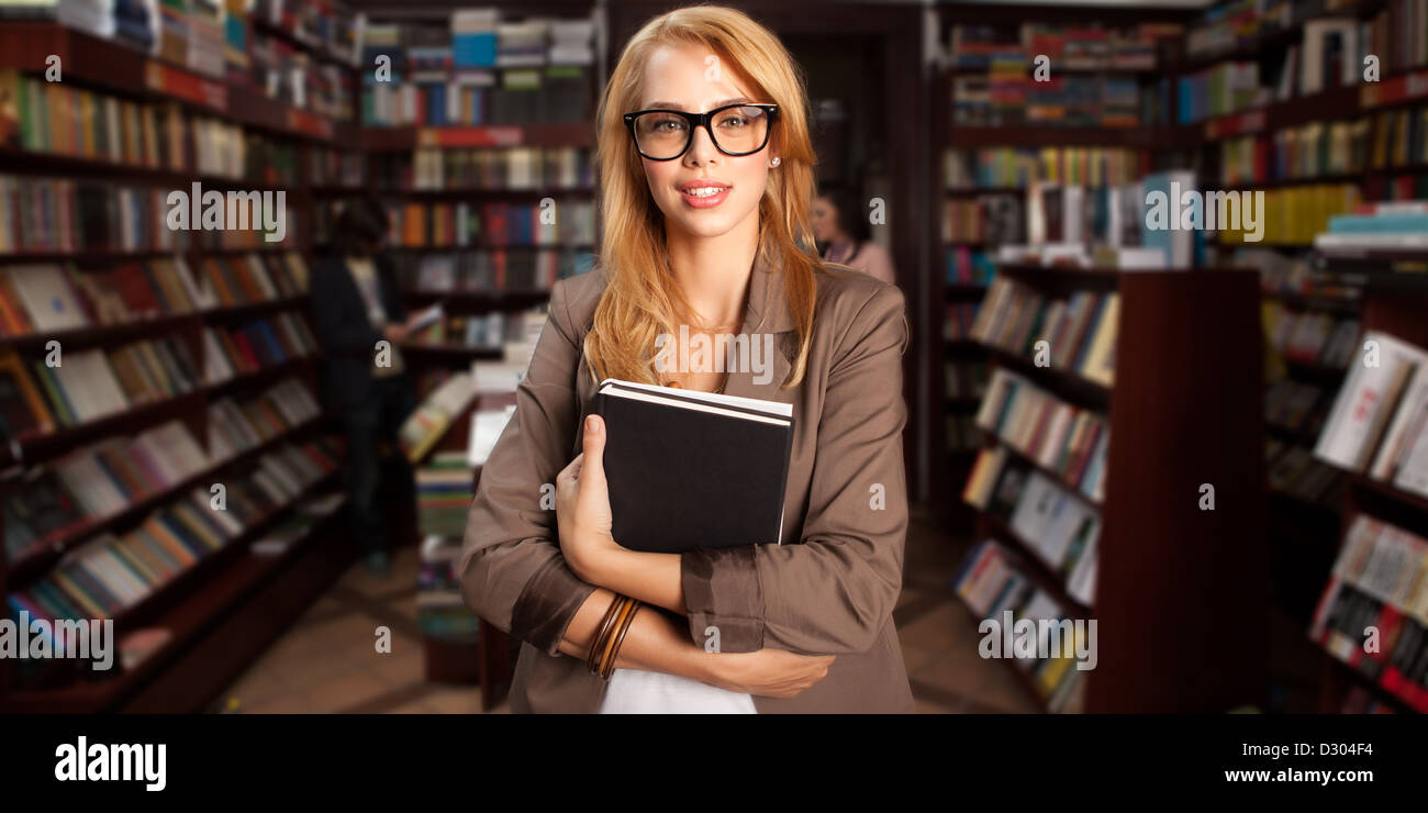 close-up of young attractive caucasian girl with geeky eyeglasses holding two books in her arms with many bookshelves - Stock Image