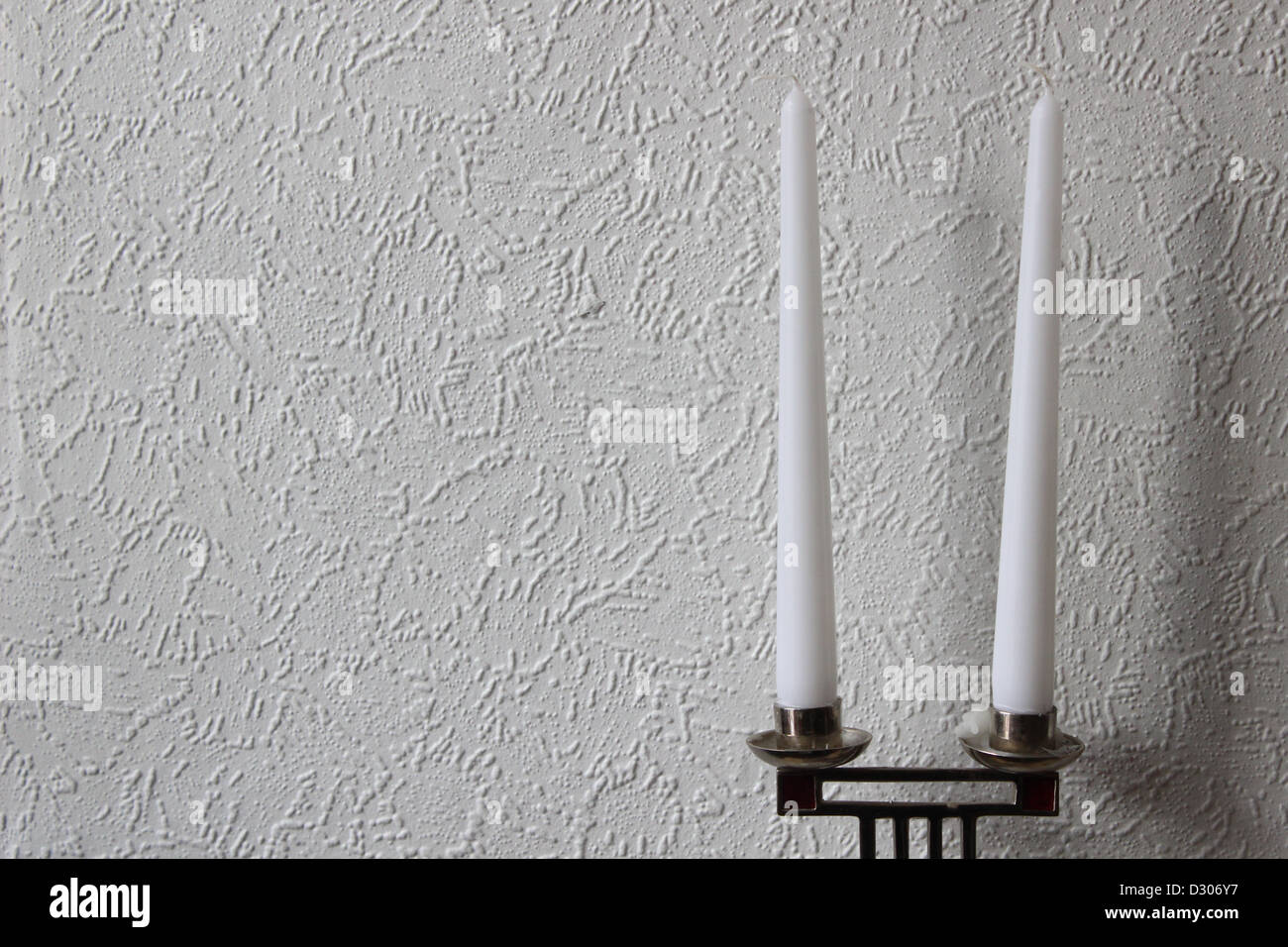 2 candle sticks against plane white wall. - Stock Image