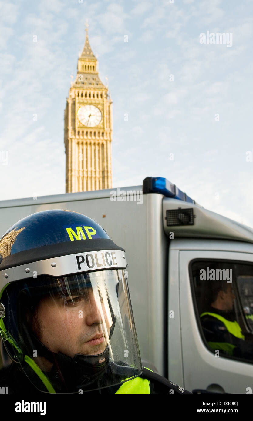 Police officer in a riot helmet demonstration protest in London, UK with Big Ben behind - Stock Image