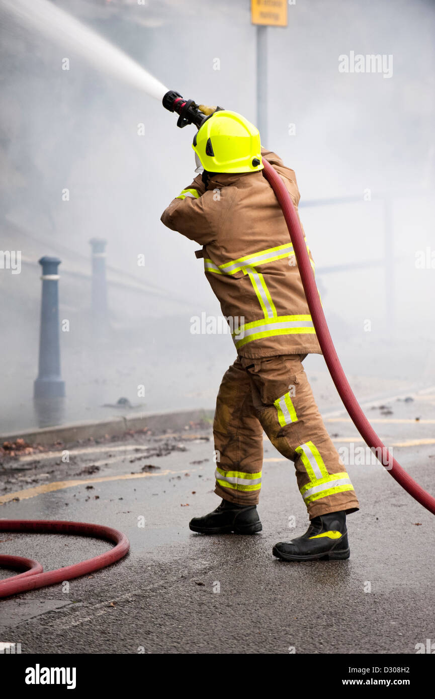 Firefighter tackles a blaze in England, UK - Stock Image