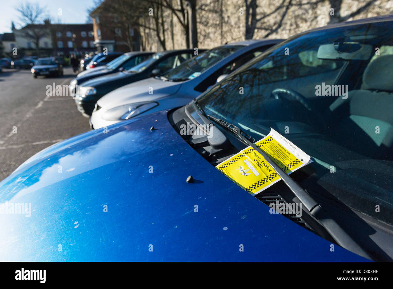 A parking ticket on the windscreen of a vehicle in a car park. - Stock Image