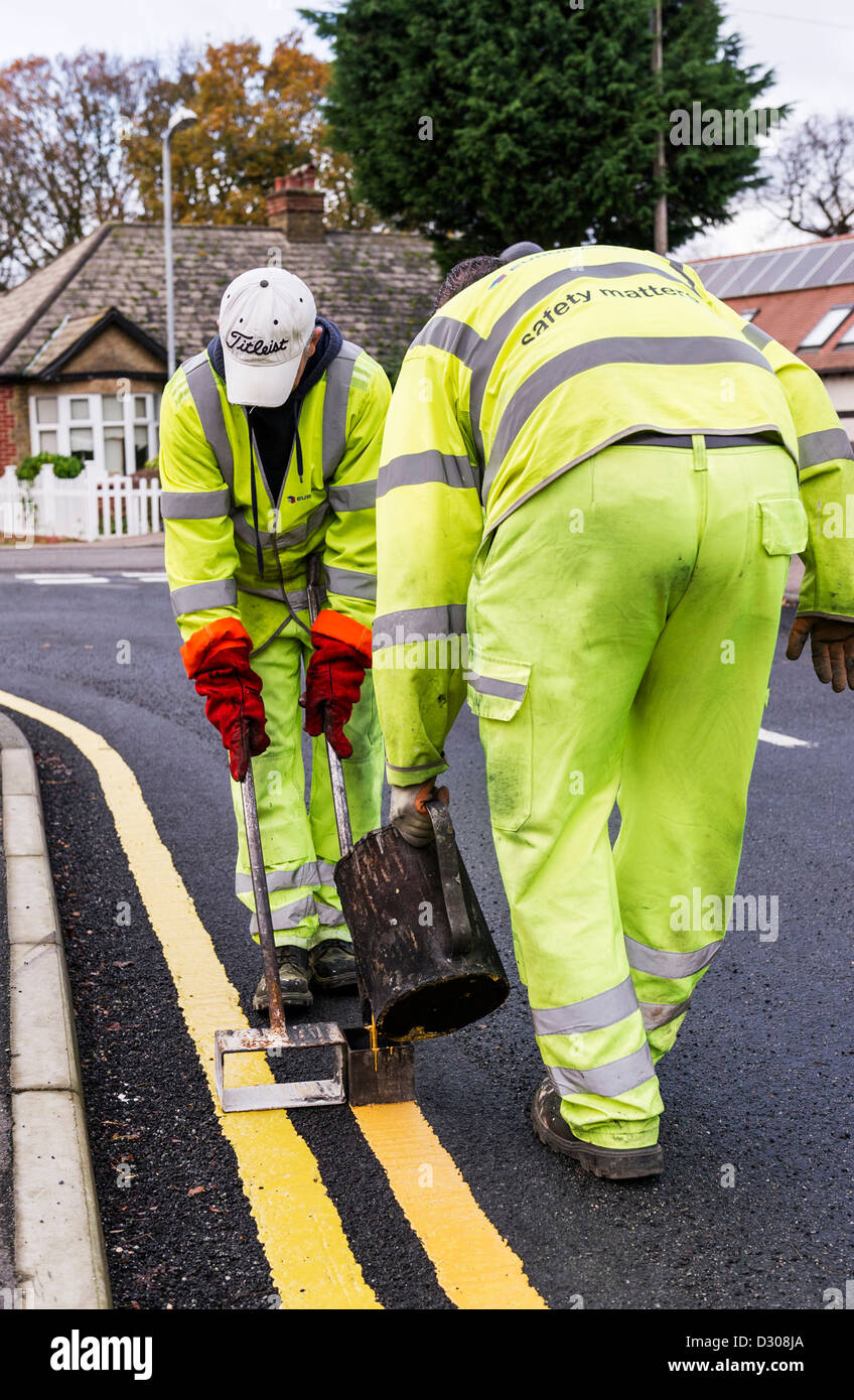 Road workers laying down double yellow lines road markings on a road, UK - Stock Image