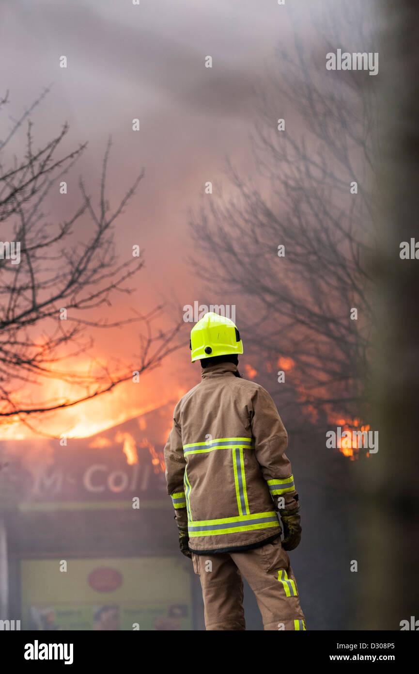 Fireman assess a burning shop building blazing in England, UK - Stock Image