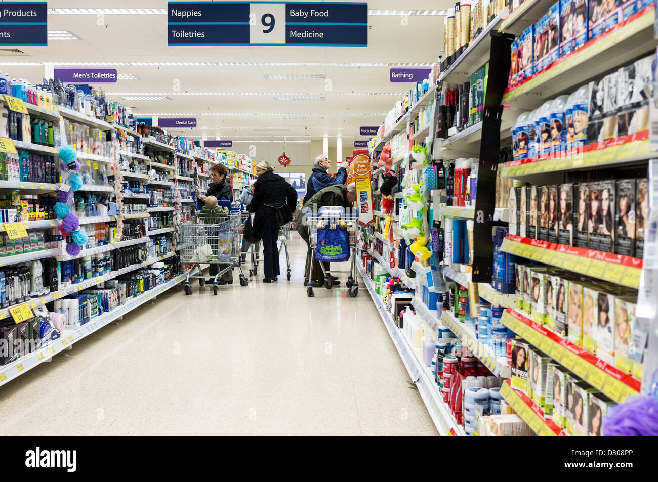Supermarket aisle and shelves - Shoppers in a Tesco supermarket - Stock Image