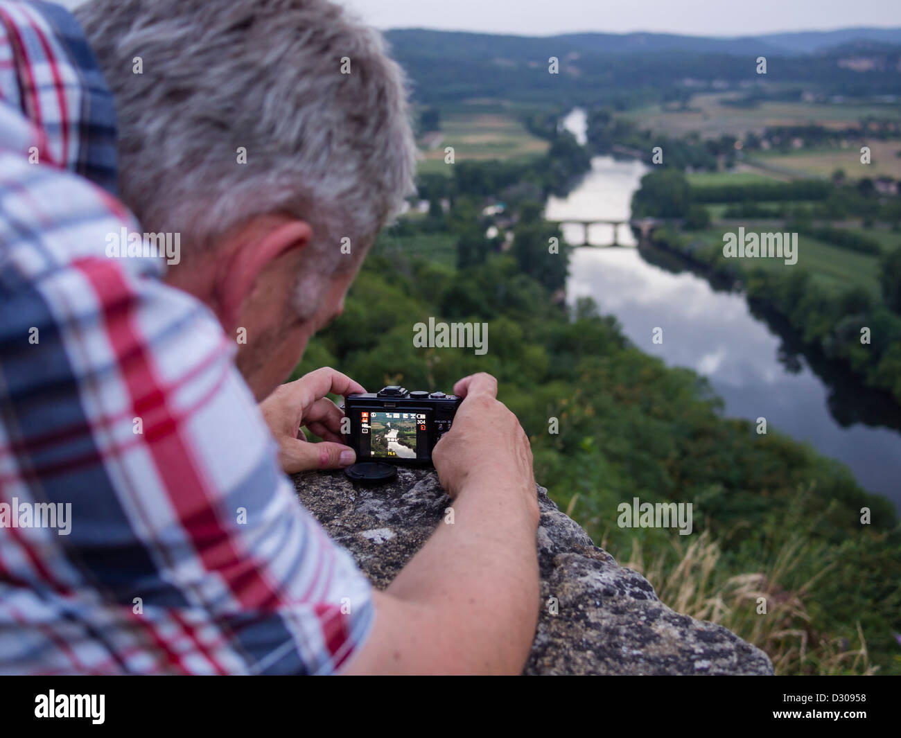 A tourist takes a photo of the river Dordogne flowing through the Périgord landscape in Southern France. - Stock Image