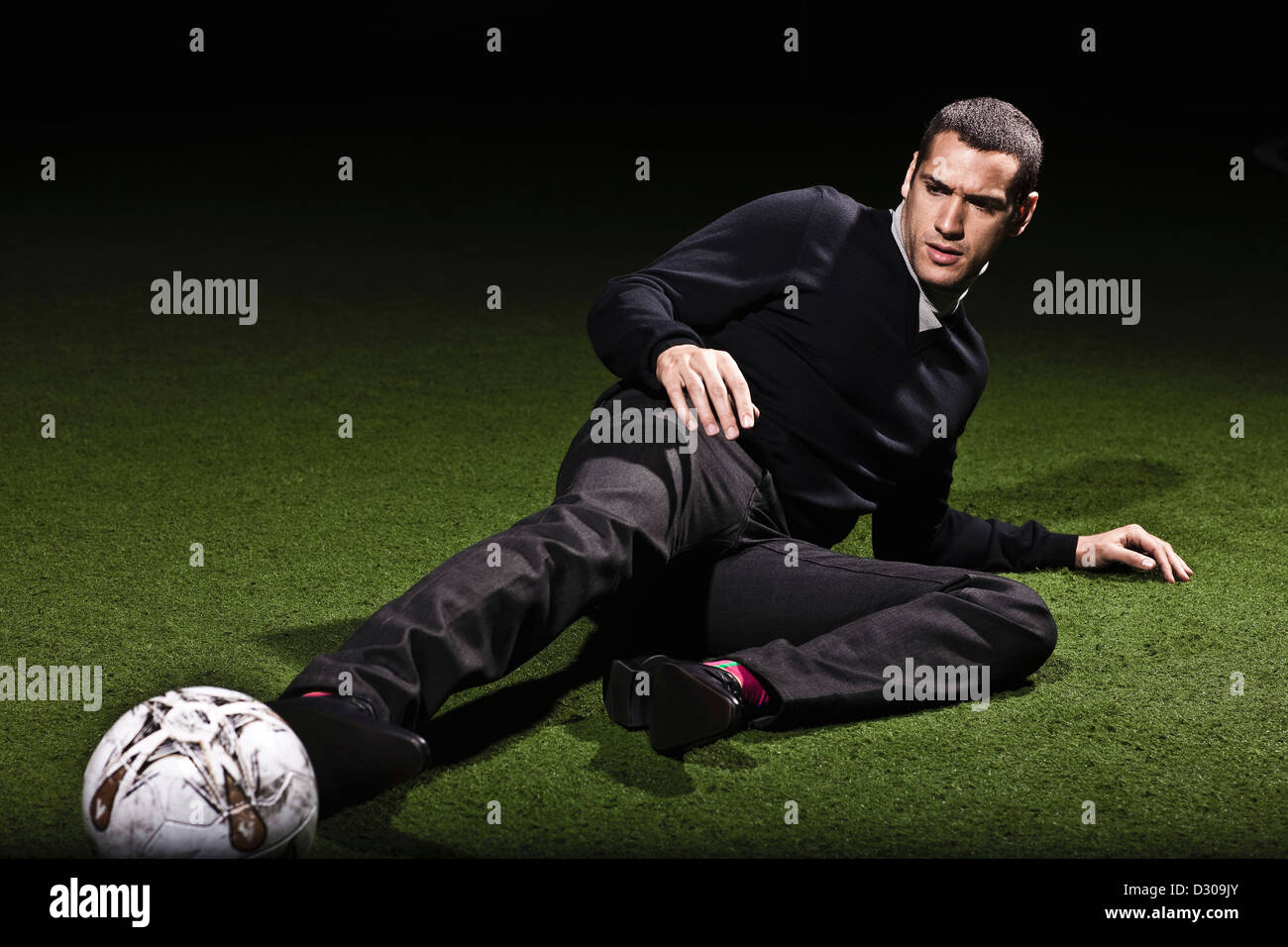 Footballer reaching for ball on astroturf - Stock Image