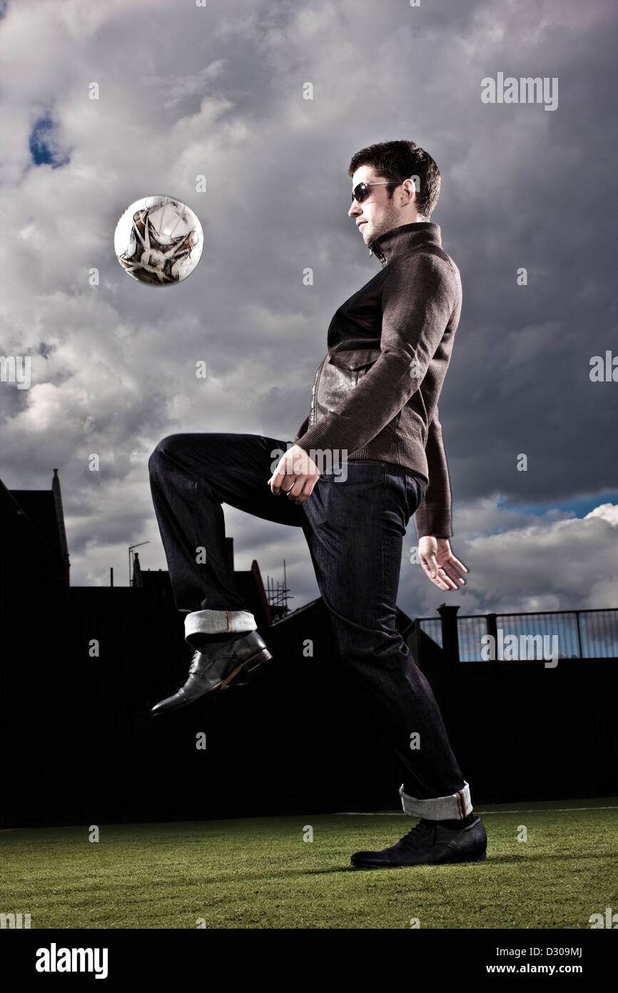 Footballer bouncing ball off his knee - Stock Image