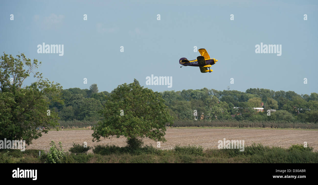 Small biplane flying over beautiful English countryside. - Stock Image