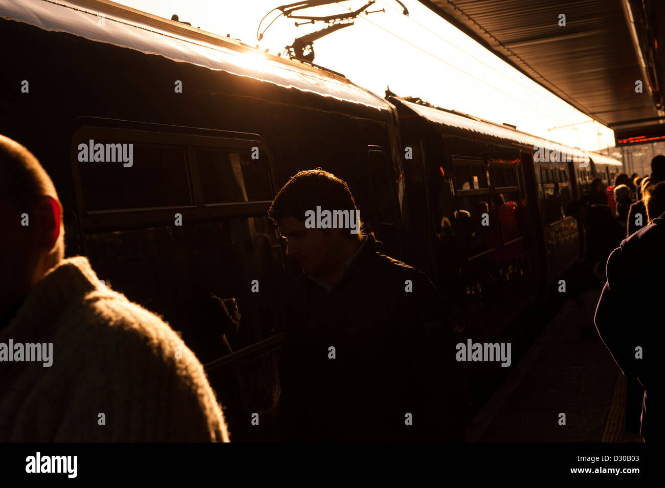 Silhouettes of passengers walking along a busy railway station platform in England. - Stock Image
