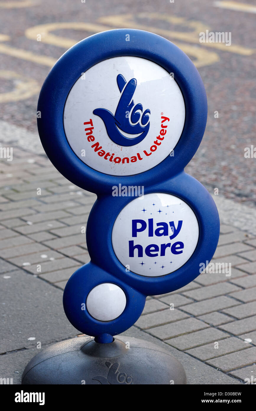 uk national lottery play here sign on the footpath outside a shop in the uk - Stock Image